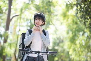 ヘルメットを付けているフードデリバリーの配達員の女性の写真素材 [FYI04566209]