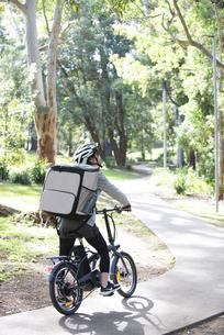 自転車に乗ったフードデリバリーの配達員の女性の写真素材 [FYI04566210]