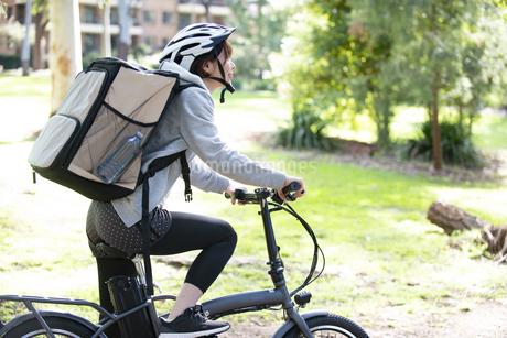 自転車に乗ったフードデリバリーの配達員の女性の写真素材 [FYI04566212]