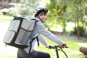 自転車に乗ったフードデリバリーの配達員の女性の写真素材 [FYI04566213]