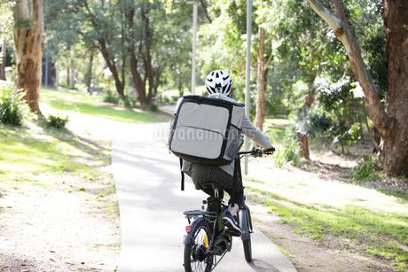 自転車に乗ったフードデリバリーの配達員の後ろ姿の写真素材 [FYI04566214]