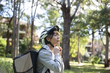 ヘルメットを付けているフードデリバリーの配達員の女性の写真素材 [FYI04566217]