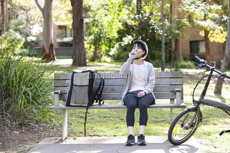 ベンチで休憩をしているフードデリバリーの配達員の女性の写真素材 [FYI04566226]