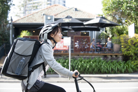 自転車に乗ったフードデリバリーの配達員の女性の写真素材 [FYI04566233]