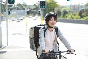 自転車に乗ったフードデリバリーの配達員の女性の写真素材 [FYI04566238]