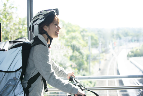 フードデリバリーの配達員の女性の横顔の写真素材 [FYI04566239]