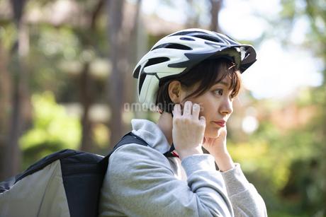 ヘルメットを付けているフードデリバリーの配達員の女性の写真素材 [FYI04566241]