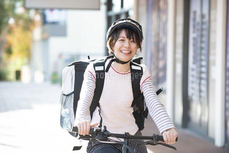 自転車に乗ったフードデリバリーの配達員の女性の写真素材 [FYI04566242]