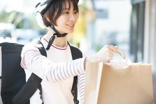 デリバリーの商品を差し出している配達員の女性の写真素材 [FYI04566268]
