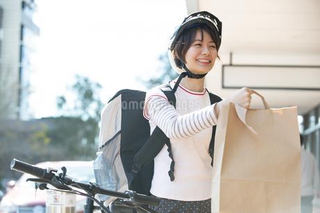 デリバリーの商品を差し出している配達員の女性の写真素材 [FYI04566269]