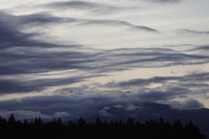 夕暮れの空にたなびく雲とシルエットの山並みの写真素材 [FYI04566395]