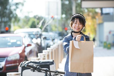 デリバリーの商品を差し出している配達員の女性の写真素材 [FYI04566921]