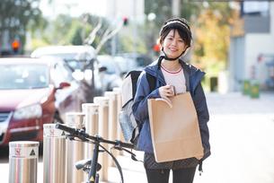 デリバリーの商品を持っている配達員の女性の写真素材 [FYI04566923]