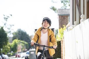 自転車に乗ったフードデリバリーの配達員の女性の写真素材 [FYI04566924]