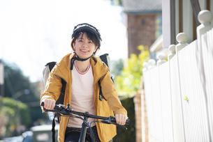 自転車に乗ったフードデリバリーの配達員の女性の写真素材 [FYI04566925]