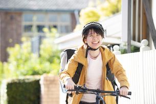 自転車に乗ったフードデリバリーの配達員の女性の写真素材 [FYI04566926]