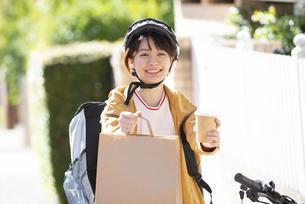デリバリーの商品を差し出している配達員の女性の写真素材 [FYI04566927]