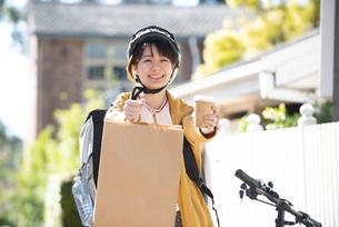 デリバリーの商品を差し出している配達員の女性の写真素材 [FYI04566928]