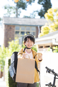 デリバリーの商品を差し出している配達員の女性の写真素材 [FYI04566929]