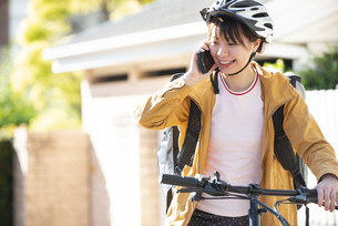 スマホで電話をしているフードデリバリーの配達員の女性の写真素材 [FYI04566933]