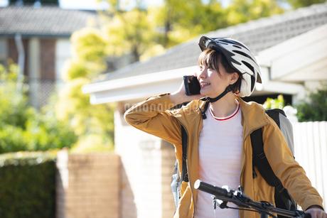 スマホで電話をしているフードデリバリーの配達員の女性の写真素材 [FYI04566934]