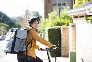 自転車に乗ったフードデリバリーの配達員の女性の写真素材 [FYI04566940]