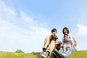 青空を背景にペットの犬と子供を抱いて芝に座る家族の写真素材 [FYI04567498]