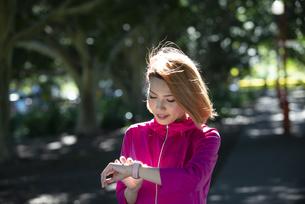 運動中にスマートウォッチを見ている女性の写真素材 [FYI04569010]