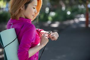 ヨガマットを持ってスマートウォッチを見ている女性の写真素材 [FYI04569085]