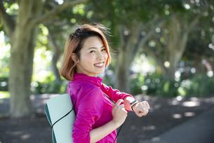 ヨガマットを持ってスマートウォッチを付けている女性の写真素材 [FYI04569086]