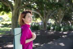 公園でヨガマットを持っている女性の写真素材 [FYI04569118]
