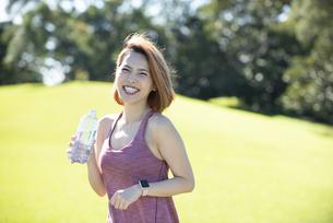 水の入ったボトルを持って笑っている女性の写真素材 [FYI04569142]