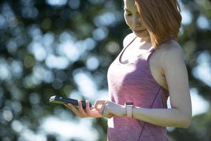 スマホとスマートウォッチを見ている女性の写真素材 [FYI04569329]