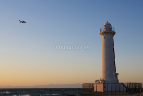 夕日に照らされた灯台と飛行機の写真素材 [FYI04570379]