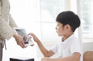 タブレットPCを見る小学生の男の子の写真素材 [FYI04570828]