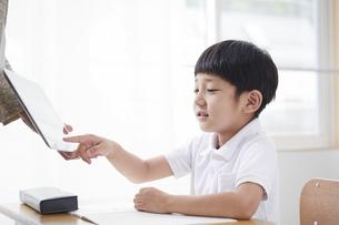 タブレットPCを見る小学生の男の子の写真素材 [FYI04570829]