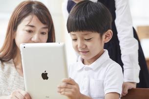 タブレットPCを見る小学生の男の子の写真素材 [FYI04570841]