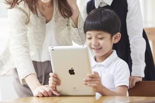 タブレットPCを見る小学生の男の子の写真素材 [FYI04570846]