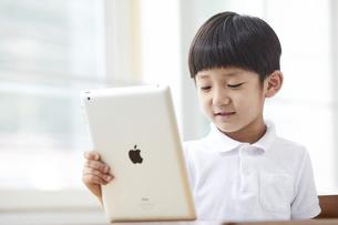 タブレットPCを見る小学生の男の子の写真素材 [FYI04570850]