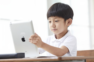 タブレットPCを見る小学生の男の子の写真素材 [FYI04570854]