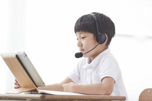 タブレットPCを見る小学生の男の子の写真素材 [FYI04570858]