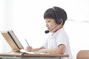 タブレットPCを見る小学生の男の子の写真素材 [FYI04570859]