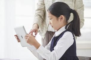 タブレットPCを見る小学生の女の子の写真素材 [FYI04570879]