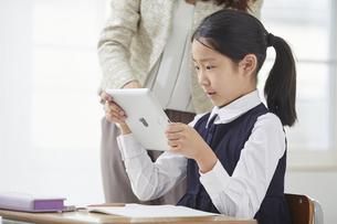 タブレットPCを見る小学生の女の子の写真素材 [FYI04570880]