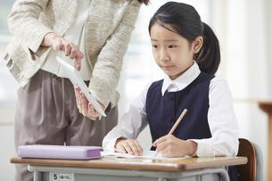 タブレット端末で勉強する制服を着た小学生の女の子と先生の写真素材 [FYI04570906]