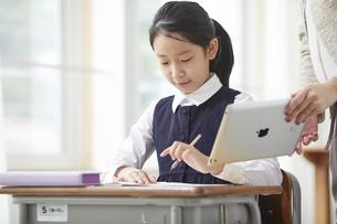 タブレット端末で勉強する制服を着た小学生の女の子と先生の写真素材 [FYI04570908]