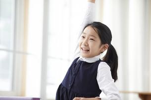 手を挙げる制服を着た小学生の女の子の写真素材 [FYI04570916]