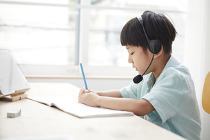 タブレットPCで勉強するインカムをつけた小学生の男の子の写真素材 [FYI04570940]