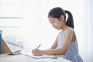 タブレットPCで勉強する小学生の女の子の写真素材 [FYI04570941]
