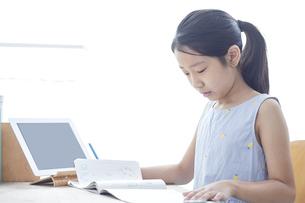 タブレットPCで勉強する小学生の女の子の写真素材 [FYI04570943]